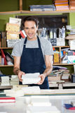 Confident Male Worker Holding Papers At Workbench Royalty Free Stock Image