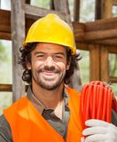 Confident Male Worker With Pipe At Construction Stock Photo