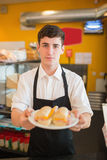 Confident male worker with sandwich  in bakery. Portrait of confident male worker with sandwich standing in bakery Stock Images