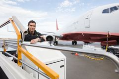 Confident Male Worker Sitting On Luggage Conveyor Truck. Portrait of confident male worker sitting on luggage conveyor truck against airplane at airport Royalty Free Stock Photos