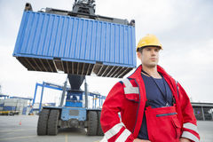 Confident male worker standing in front of freight vehicle at shipyard Royalty Free Stock Photo