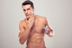 Confident man applying facial lotion. Over gray background Stock Photo