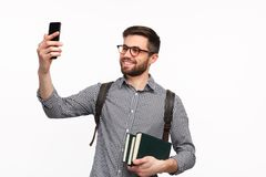 Confident man with books taking selfie. Smiling handsome student in glasses holding few books and taking selfie with smartphone on white Stock Image