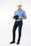 Confident man building engineer in hard hat writing in folder Stock Image
