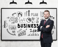 Confident man and business idea. Portrait of a confident businessman standing with crossed arms nea a business idea sketch drawn on a whiteboard Royalty Free Stock Image