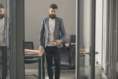 Confident man in casual suit at working place. Bearded man look out room door. Businessman in modern office with glass. Walls. Business and office lifestyle Stock Image
