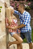 Confident man dating young blonde girl outdoors. Confident casual handsome men dating young blonde girl outdoors, smiling, leaning against wall royalty free stock photos