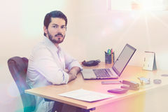 Confident man at desk. Young entrepreneur looking at camera. Window light leak. Confident Royalty Free Stock Image