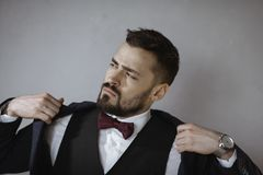 Confident Man Dressing in Suit. Man`s style. Elegant brutal bearded man getting ready, dressing suit against gray grunge background. Fashion vogue photo. Close stock photography