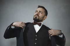 Confident Man Dressing in Suit. Man`s style. Elegant brutal bearded man getting ready, dressing suit against gray grunge background. Fashion vogue photo royalty free stock image