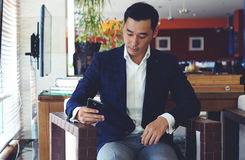 Confident man entrepreneur using cell telephone while relaxing in cafe Royalty Free Stock Image
