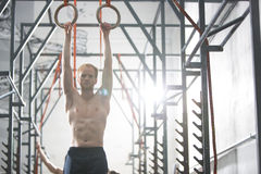 Confident man exercising with gymnastic rings in crossfit gym Stock Images