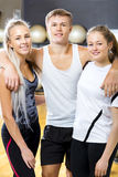 Confident Man With Female Friends Standing In Gym Stock Photo