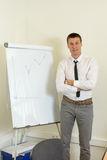 Confident man in front of a flipchart. Confident young man in front of a flipchart Stock Photos