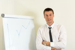 Confident man in front of a flipchart. Confident young man in front of a flipchart Stock Photography