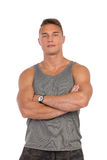 Confident Man In Gray Tank Top. Young muscular man in gray tank top posing with arms crossed. Waist up studio shot isolated on white Royalty Free Stock Photo