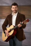 Confident man with guitar Royalty Free Stock Image