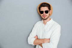 Confident man in hat and sunglasses standing with arms crossed. Confident young man in hat and sunglasses standing with arms crossed over grey background Royalty Free Stock Photography