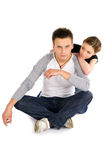 Confident Man with His Girlfriend. Young confident man sitting on the ground, his girlfriend lean on him with love, isolated on white background royalty free stock photos