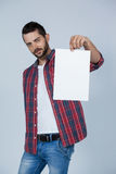 Confident man holding a blank placard. Against grey background Stock Photo