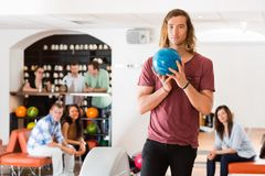 Confident Man Holding Bowling Ball in Club Stock Photo