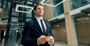 Confident man holding coffee cup and using his smart phone while walking in hall. Coffee break on go. confident man holding coffee cup and using his smart phone Stock Images