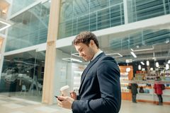 Confident man holding coffee cup and using his smart phone while walking in hall. Coffee break on go. confident man holding coffee cup and using his smart phone Royalty Free Stock Images