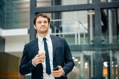 Confident man holding coffee cup and using his smart phone while walking in hall. Young businessmen going to the work in the morning with phone and coffee cup Royalty Free Stock Photo
