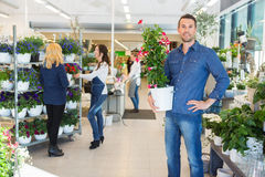 Confident Man Holding Flower Plant In Shop Stock Images