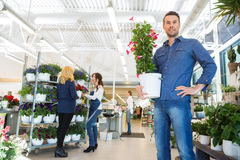 Confident Man Holding Flower Plant In Shop Stock Photo