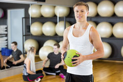 Confident Man Holding Medicine Ball While Friends Resting In Gym Stock Image