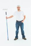 Confident man holding paint roller on white background Royalty Free Stock Image
