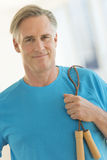 Confident Man With Jump Rope Smiling In Gym Royalty Free Stock Photos