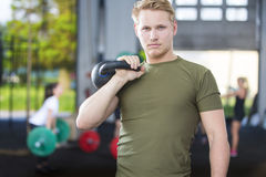 Confident man with kettlebell at fitness gym Stock Photos