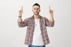 Confident man always knew he will win. Studio shot of serious and cool young male student raising hands and pointing up royalty free stock photos