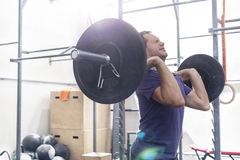 Confident man lifting barbell in crossfit gym Stock Photos