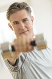 Confident Man Lifting Weights At Health Club Stock Photo