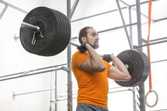 Confident man looking away while lifting barbell in crossfit gym Royalty Free Stock Image