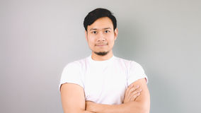 A confident man looking at the camera. An asian man with white t-shirt and grey background royalty free stock images