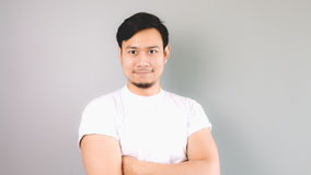 A confident man looking out. An asian man with white t-shirt and grey background royalty free stock photos