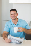 Confident man with newspaper holding coffee cup Royalty Free Stock Images