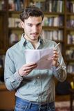 Confident man with notes. Young man in shirt holding pen with papers and looking provocatively at camera Stock Photo