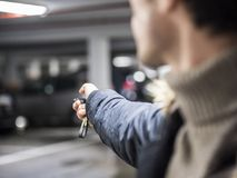 Confident man on parking setting car alarm. Young trendy man in outerwear standing on parking using alarm remote control Royalty Free Stock Images