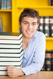 Confident Man With Piled Books Smiling In College Stock Images