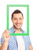 Confident man posing behind a picture frame Royalty Free Stock Photography