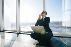 Confident man pray and sitting with laptop in office Royalty Free Stock Photos