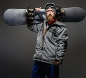 Confident man with red beard wearing a full equipment holding a snowboard on his shoulder, isolated on a dark background. Confident man with a red beard wearing stock photos