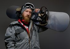 Confident man with red beard wearing a full equipment holding a snowboard on his shoulder, isolated on a dark background. Confident man with a red beard wearing royalty free stock image