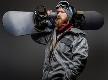 Confident man with a red beard wearing a full equipment holding a snowboard on his shoulder, looking away with a serious. Look royalty free stock images