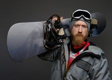 Confident man with a red beard wearing a full equipment holding a snowboard on his shoulder, looking at a camera with a. Serious look royalty free stock photos